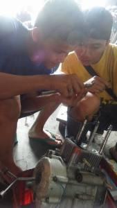 siswa kursus sedang fokus mengukur mesin balap